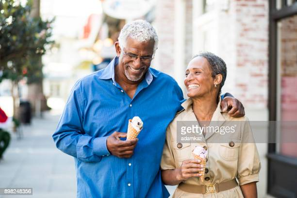 african american senior couple on the town with ice cream - happy family stock photos and pictures