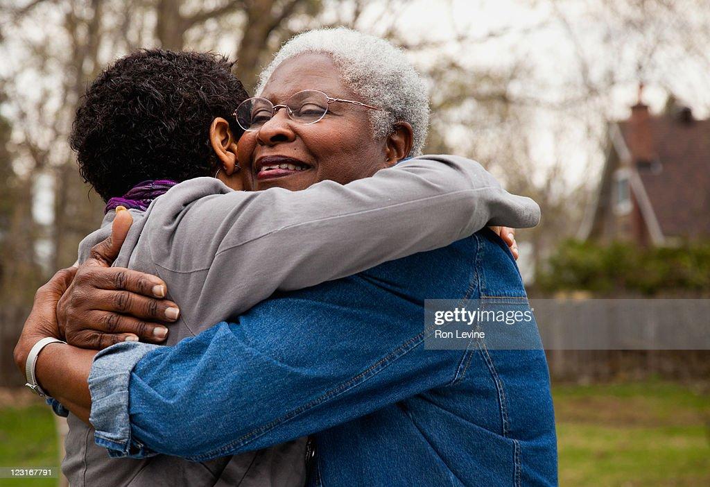 African American senior hugging her daughter : Stock Photo