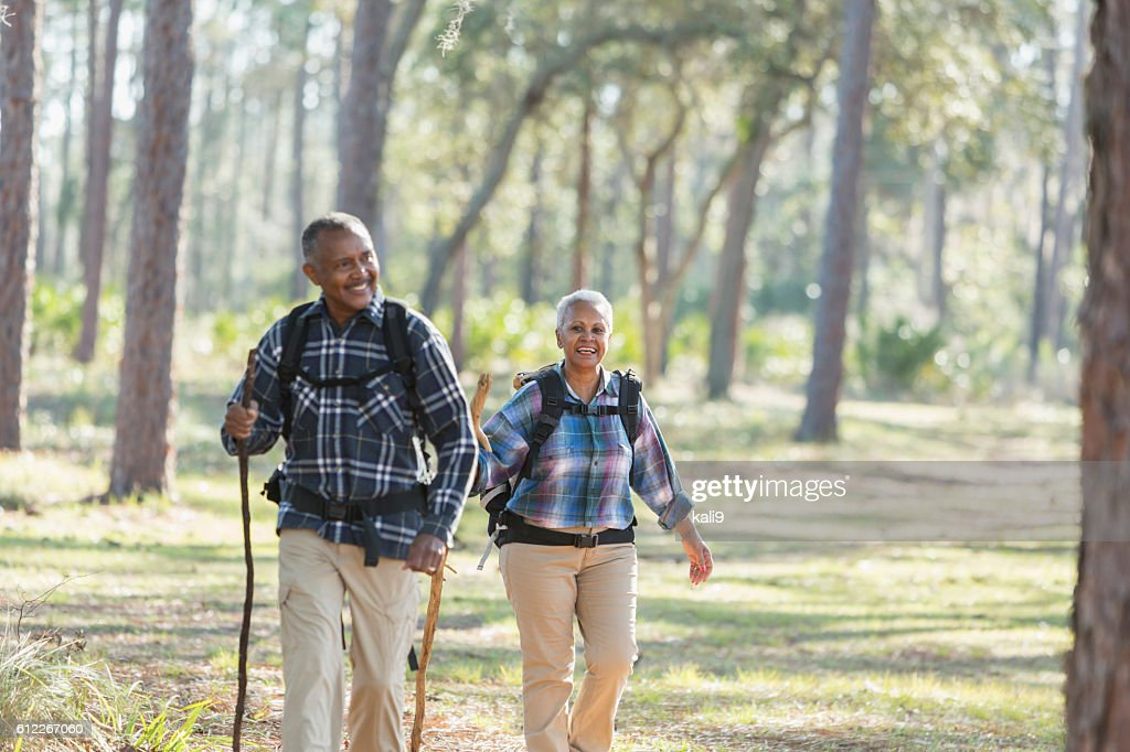 African American seniors hiking through woods : Stock Photo