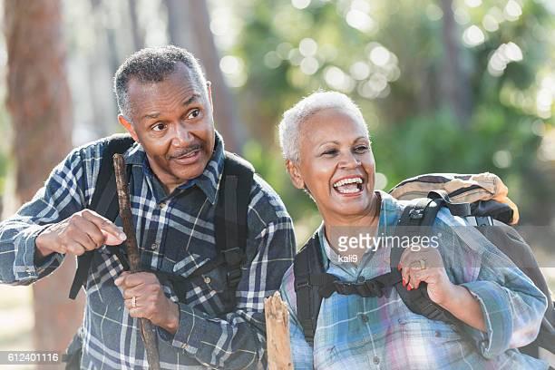 African American seniors hiking through woods