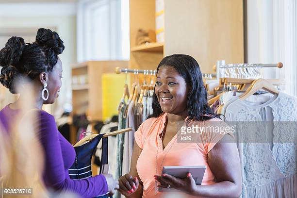 Afro-américaine shopping dans le magasin et Vendeuse