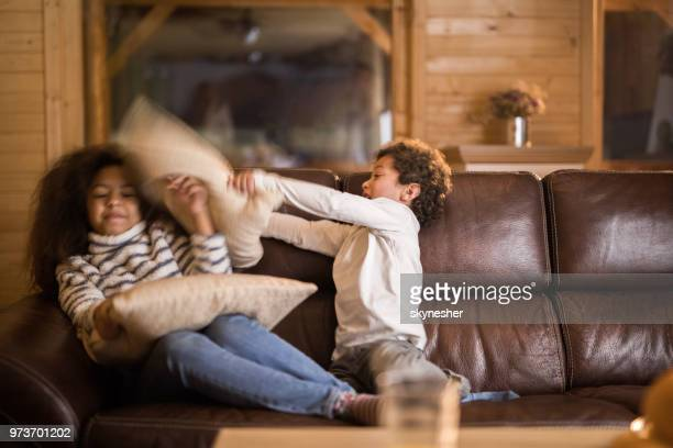 african american siblings having fun during a pillow fight at home. - sister stock pictures, royalty-free photos & images