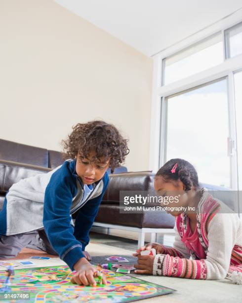 african american siblings playing board game - game board stock photos and pictures