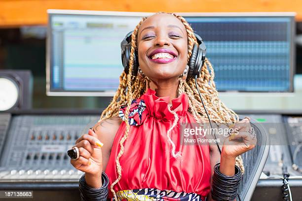African American singer listening to track in studio