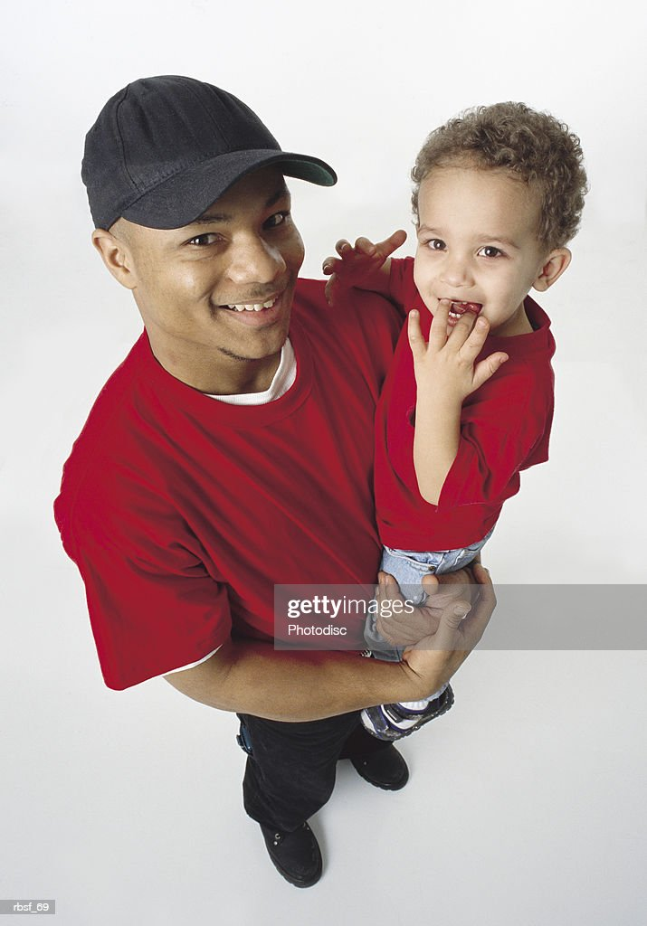 african american single father holds young son and smiles wearing baseball cap and red shirt : Foto de stock