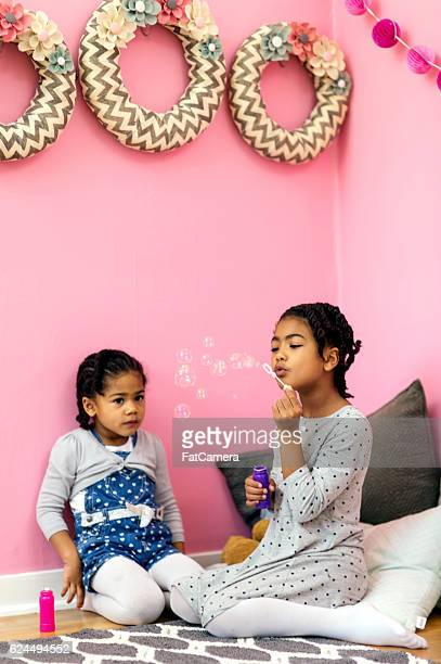 African American sisters blowing bubbles in their pink bedroom