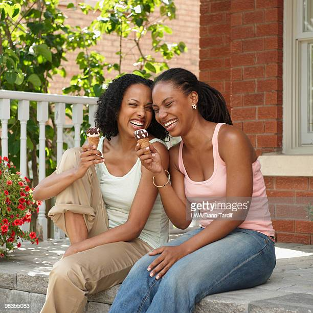 African American sisters eating ice cream cones