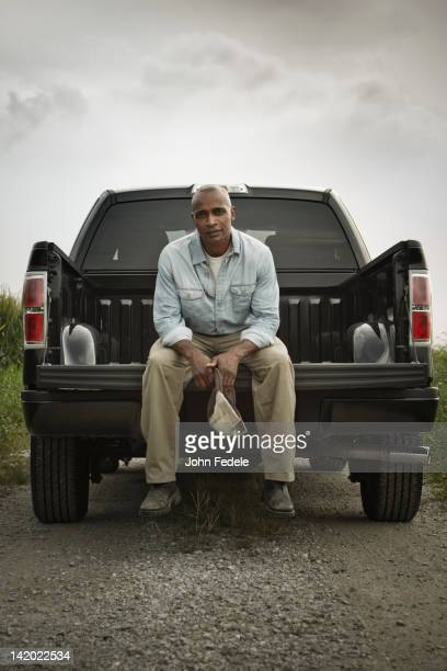 African American sitting on back of pick-up truck