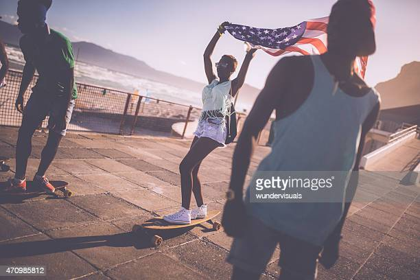 African American skateboarder flying an American flag while skating