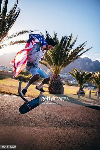 Pattinaggio di americano africano facendo gradino mentre si tiene bandiera americana