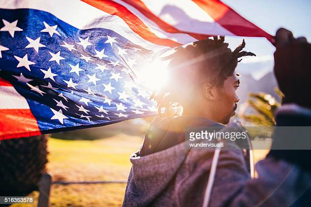 African American Skater Holding American Flag During Sunset