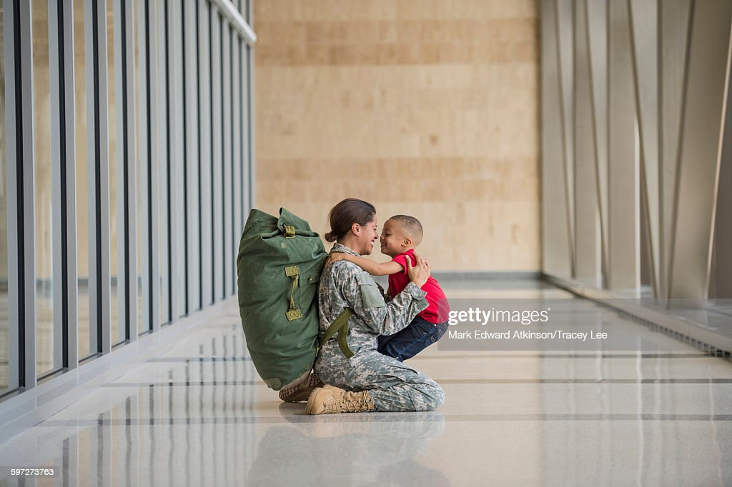 African American soldier hugging son in airport : Stock Photo