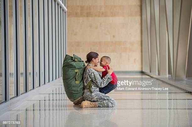 african american soldier hugging son in airport - army soldier stock photos and pictures