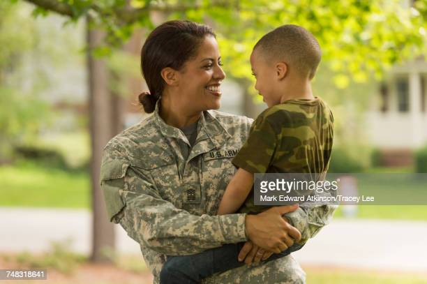 african american soldier mother carrying son - army soldier stock photos and pictures