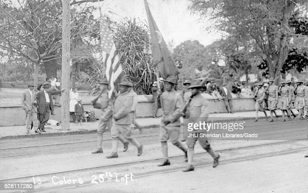 African American soldiers who are part of the 25th Infantry Division of the United States Army located in Hawaii are walking in a parade and holding...