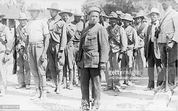 African American soldiers with neutral expressions some of whom carry weaponry stand in rows outdoors 1915