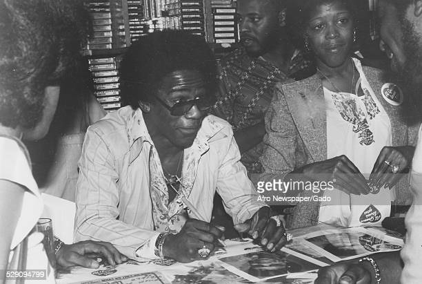 African American soul singer Al Green wearing Afro haircut, signing autographs, 1975.