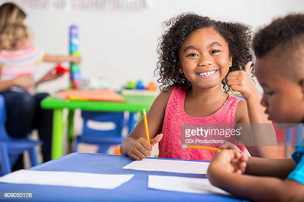 African American student gives thumbs up in class