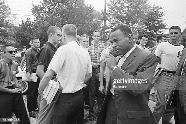 African American student James Meredith walks across the University of Mississippi campus after class amid the stares and jeers of fellow students....
