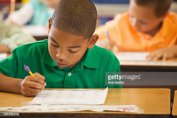 African American student studying at desk in classroom