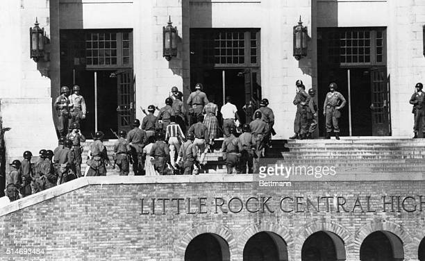 African American students are escorted by soldiers into Little Rock's Central High School on the first full day of integration