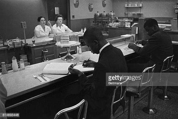 African American students from Saint Augustine College study while participating in a sitin at a lunch counter reserved for white customers in...