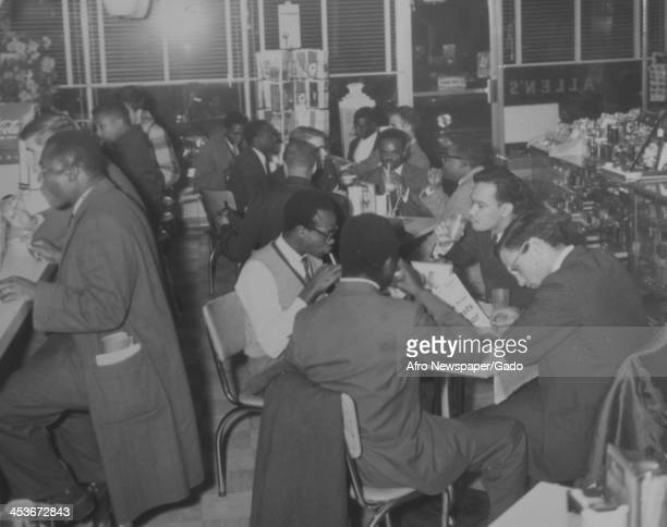 African American students from the Tuskegee Institute sit in a diner with white students from Stanford University in Alabama to protest segregation...