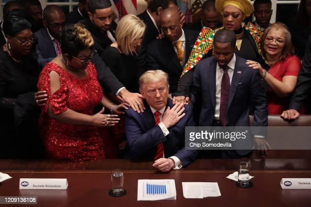 African American supporters lay their hands on US President Donald Trump as they pray for him at the conclusion of a news conference and meeting in...