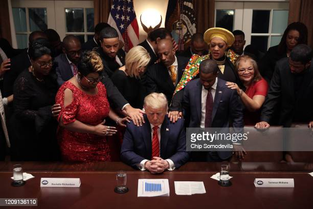 African American supporters lay their hands on U.S. President Donald Trump as they pray for him at the conclusion of a news conference and meeting in...