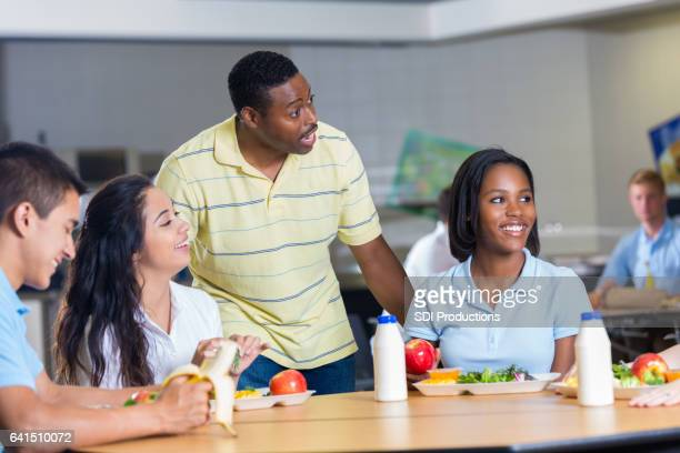 African American teacher talks with students at lunch