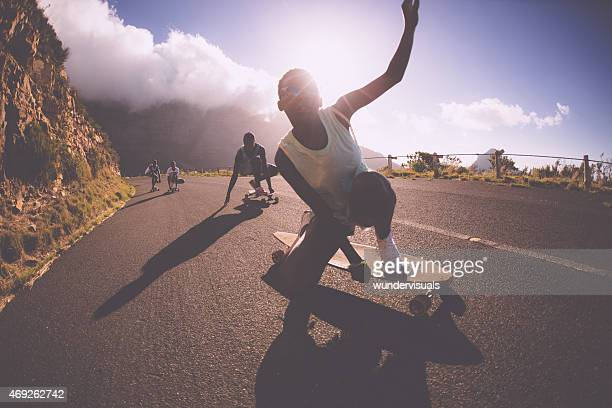african american teen girl on a longboard doing downhill racing - skating stock photos and pictures