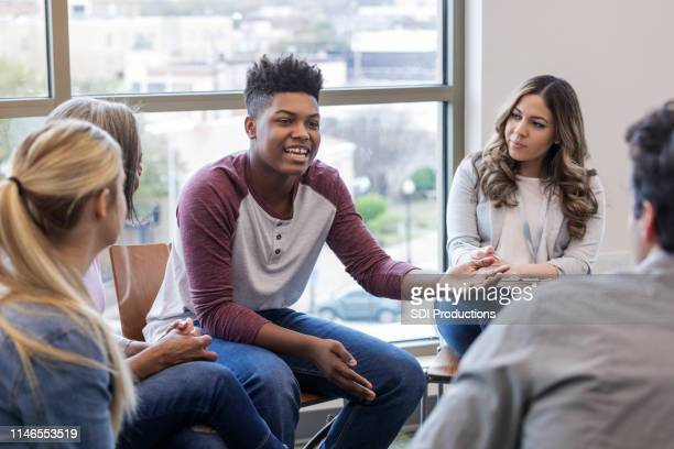 african american teen shares problem with diverse group - group therapy stock pictures, royalty-free photos & images