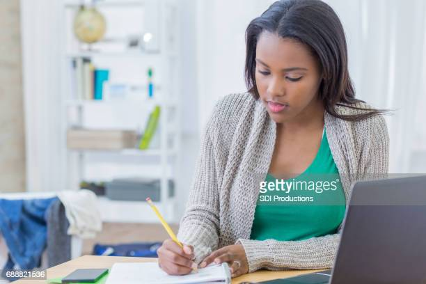 african american teenager concentrates while working on homework assignment - black girls stock photos and pictures