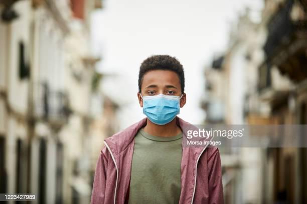 afrikaanse amerikaanse tiener met beschermend masker op de straat voor covid-19 pandemie - afro amerikaanse etniciteit stockfoto's en -beelden