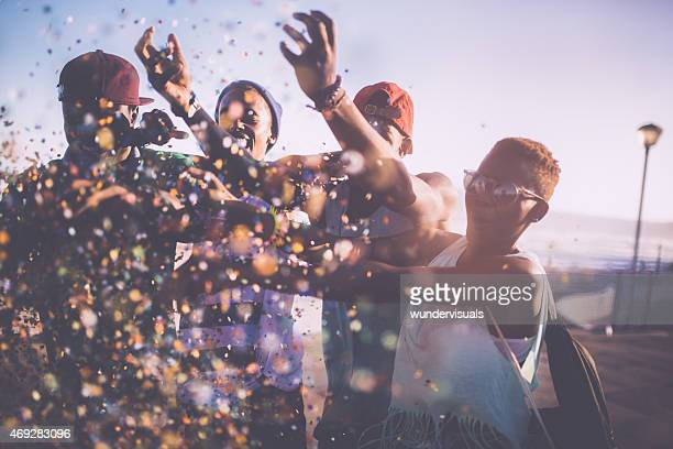 African American teenagers celebrating outdoors with colourful confetti
