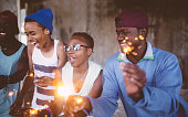 African American teens celebrating happily with sparklers