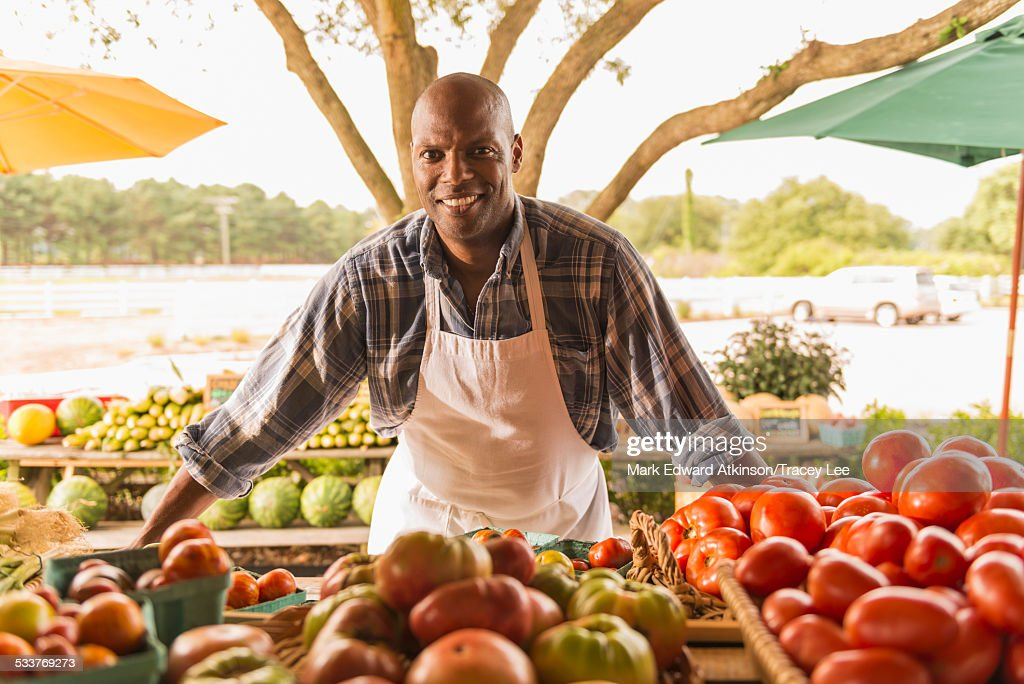 African American vendor smiling at farmers market : Foto stock