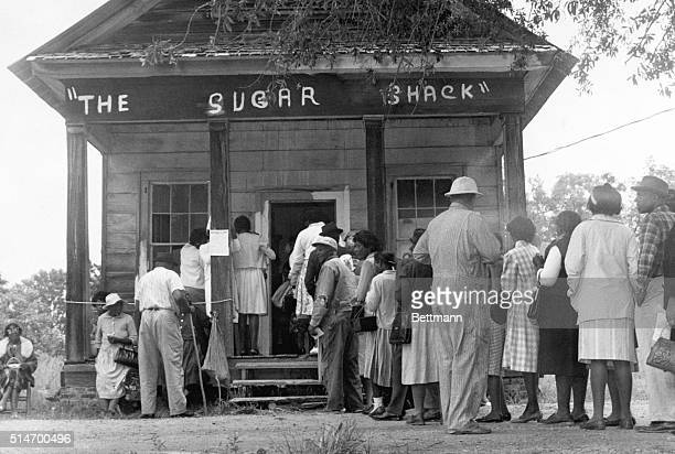 African American voters able to vote for the first time in rural Wilcox County Alabama line up in front of a polling station at The Sugar Shack a...