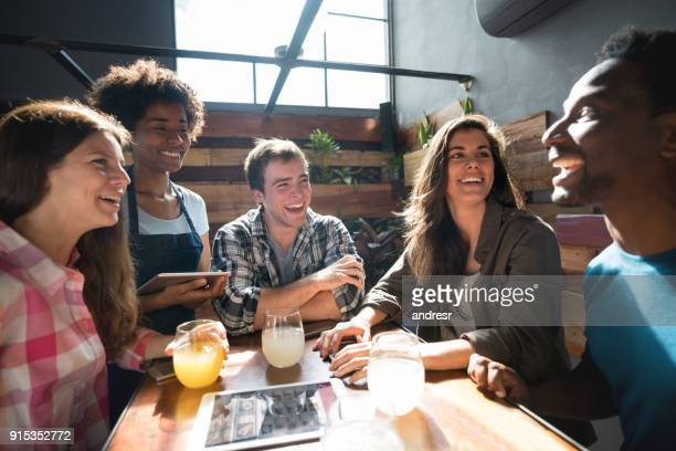 African american waitress taking the order from a group of friends while laughing and making jokes