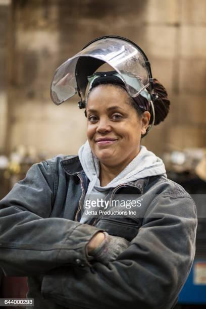 African American welder wearing mask in factory