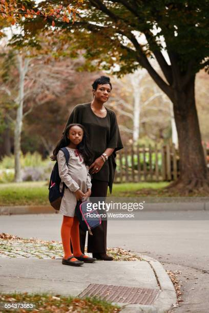 African American woman and daughter waiting for school bus