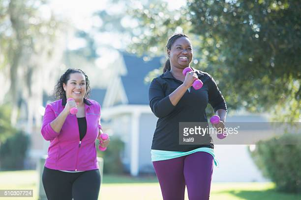 African American woman and friend running with dumbbells