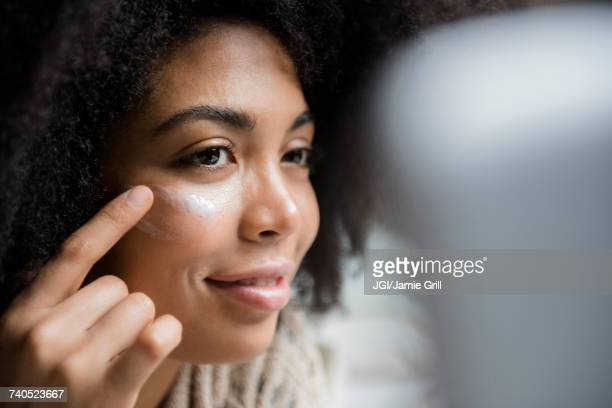 african american woman applying lotion to face - sunscreen stock photos and pictures
