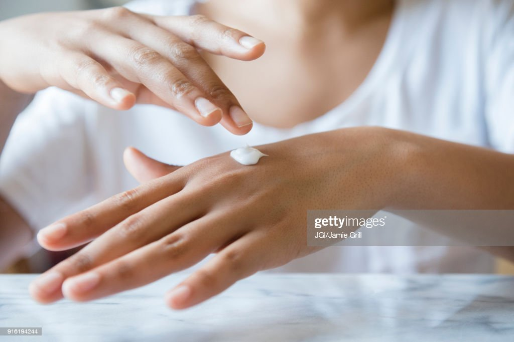 African American woman applying lotion to hand : Stock Photo