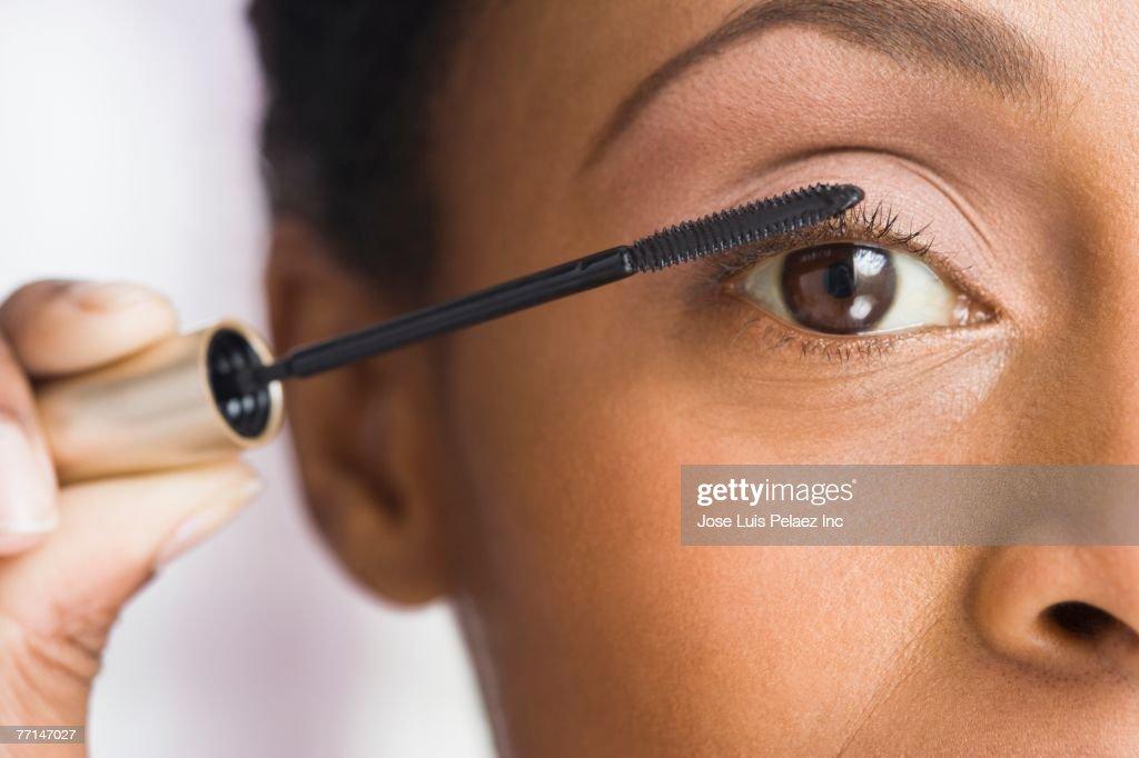 African American woman applying mascara : Stock Photo
