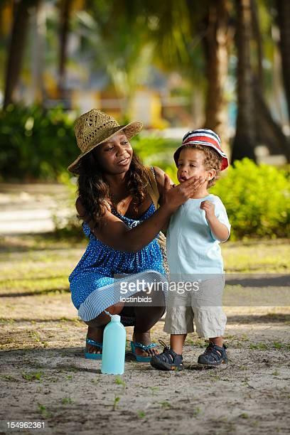 Afrikanische amerikanische Frau Anwendung Sonnenschutz Lotion für Kleinkinder