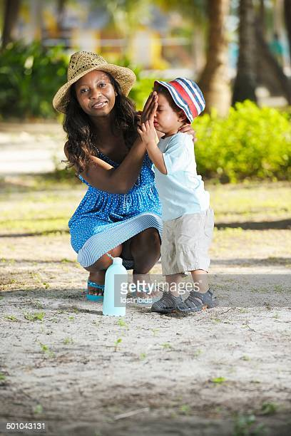 African American Woman Applying Sunscreen Lotion On Toddler