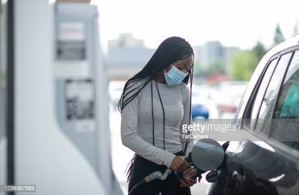african american woman at gas pump wearing mask - combustível fóssil imagens e fotografias de stock