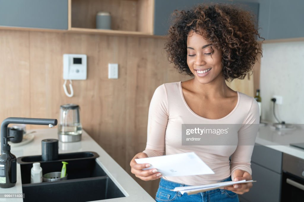 African American woman at home checking her mail : Stock Photo