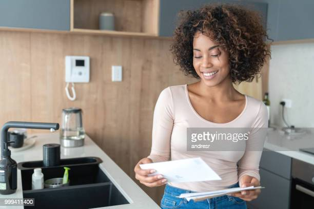 african american woman at home checking her mail - mail stock pictures, royalty-free photos & images